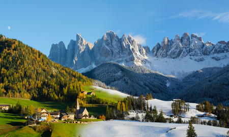 wintersport: Composite image of two photos taken two days after one another showing the change of season from fall to winter  The village of St  Magdalena or Santa Maddalena with church in front of the Geisler dolomites mountain peaks in the Val di Funes in Italy