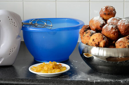 traditionally dutch: Ingredients like raisins and a hand mixer for baking oliebollen, oil balls or donut balls, a dutch pastry traditionally eaten on New Years Eve in the Netherlands.