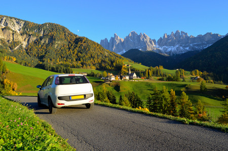 car rental: a white car in autumn through the Funes valley in Dolomites area in South Tyrol, Italy. Stock Photo