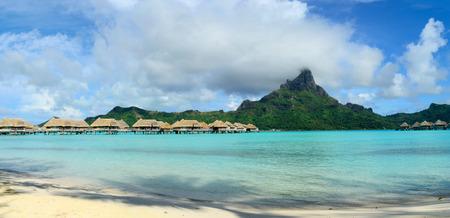 Vue panoramique sur les bungalows sur pilotis de luxe dans un lieu de villégiature dans le lagon bleu clair avec en arrière-plan l'île tropicale de Bora Bora, près de Tahiti, en Polynésie française.