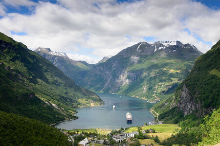 river: View over a cruise ship in the fjord Geirangerfjord, and the village Geiranger surrounded by mountains in Mre og Romsdal, Norway, seen from flydalsjuvet viewpoint. Stock Photo