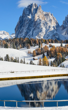 Reflection of the Langkofel (Sassolungo) Dolomites mountain top in a lake on the Seiser Alm (Alpe di Siusi) between the yellow larch trees in autumn in South Tyrol, Italy. photo