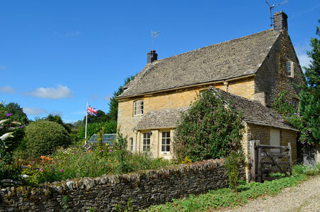 cotswold: A honey-coloured Cotswold stone English cottage with a garden full of flowers and a British flag in Upper Slaughter, Cotswolds, UK.