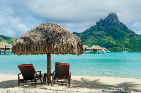 Two sunlounger chairs under a thatched parasol on a white sand beach with a view on the lagoon and the tropical island of Bora Bora, near Tahiti, in French Polynesia.