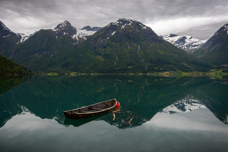 An old row boat in the still water of Oppstrynsvatnet with reflection of the mountains in a Norwegian landscape at Hjelle, Sogn og Fjordane, Norway.