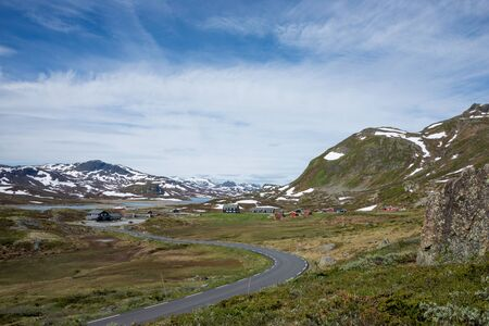 jotunheimen national park: Curvy road towards some wooden houses in a small remote village in a mountain landscape in Jotunheimen National Park, Norway. Stock Photo