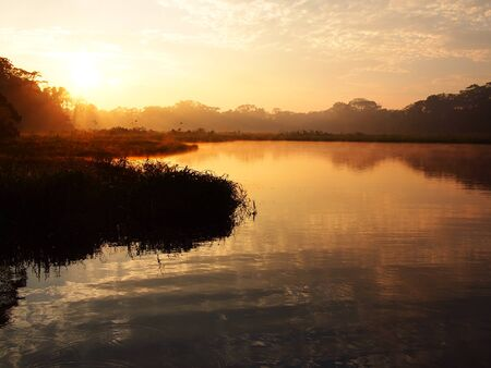peru amazon: An orange sunrise with some light fog over the water of the Tambopata river during sunrise in the Amazon rainforest in eastern Peru near the border with Brazil.