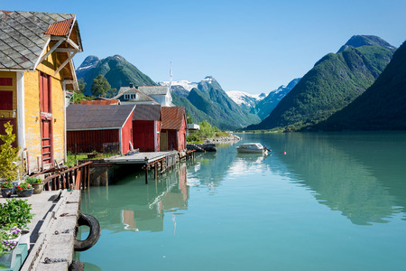 snowcapped: View over the fjord Fjaerlandsfjord and the small village of Mundal (or Fjaerland) with some snow-capped mountains, a boat, reflection in the water and yellow and red boathouses in Sogn of Fjordane, Norway.