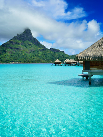 Luxury overwater honeymoon bungalows in a vacation resort in the clear blue lagoon with a view on Mt. Otemanu on the tropical island of Bora Bora, near Tahiti, in French Polynesia.