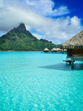 pilotis de luxe lune de miel bungalows dans une station de vacances dans le lagon bleu clair avec une vue sur le mont Otemanu sur l'île tropicale de Bora Bora, près de Tahiti, en Polynésie française. Éditoriale