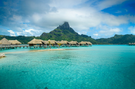 Luxury thatched roof over water bungalow resort in a vacation resort in the clear blue lagoon with a view on the tropical island of Bora Bora near Tahiti in French Polynesia.