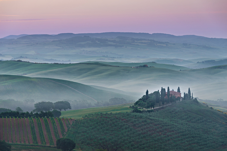 valdorcia: Foggy sunrise with a pink sky and fog between the Tuscan hills about Podere il Belvedere farmhouse in the Valdorcia Orcia Valley between Pienza and San Quirico in Tuscany, Italy. Stock Photo