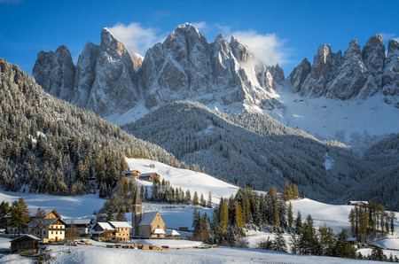 The small village of St. Magdalena or Santa Maddalena with its church covered in snow and with the Odle Geisler or Dolomites mountains behind it in the Val di Funes Valley Villnsstal in South Tyrol in Italy in winter.