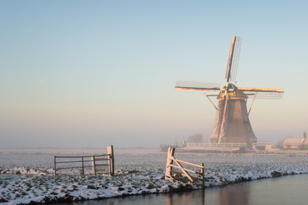 holland landscape: Winter landscape in Holland the Netherlands in a rural area with a windmill in a meadow, a fence, a canal, snow and fog at sunrise.