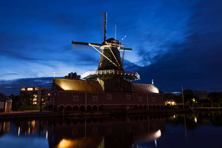 leidschendam: Windmill Salamander, a sawmill still in use in Leidschendam in the Netherlands at night under a blue sky falling on the blue hour.