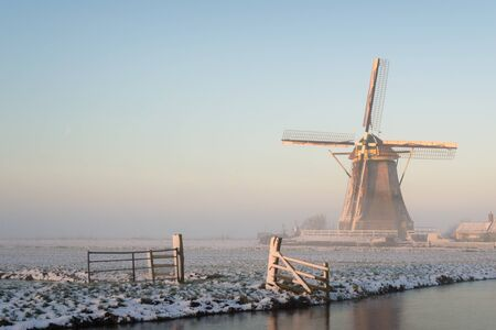 wind mills: Winter landscape in the Netherlands Holland in a rural area with a windmill in a meadow, a fence, a canal, snow and fog at sunrise. Stock Photo