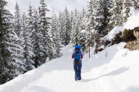 baby carrier: Tourist mother in ski gear walking in the snow in a forest with snow on the trees with her baby child on her back in a baby carrier backpack in a ski resort area in winter.