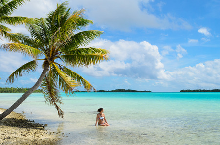 Female tourist bathing in the shallow water of the sea under a hanging palm tree on a beach on a desert island in the lagoon of Rangiroa, a tropical atoll in the pacific Bora Bora archipelago French Polynesia.