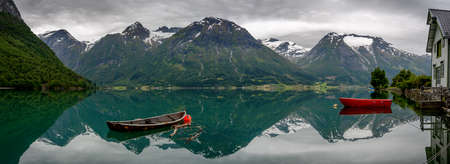 rowboats: Panorama of two old rowboats  with reflection of the mountains in the still water of Oppstrynsvatnet lake in a Norwegian landscape at Hjelle, Sogn og Fjordane, Norway.