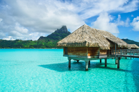 thatched roof: Luxury overwater thatched roof bungalow in a honeymoon vacation resort in the clear blue lagoon with a view on the tropical island of Bora Bora, near Tahiti, in French Polynesia.