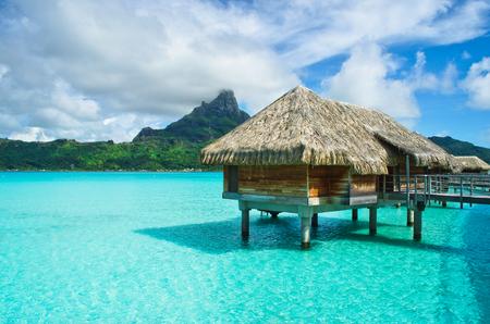 luna de miel: sobre el agua de lujo de paja bungalow de techo en un complejo de luna de miel vacaciones en la laguna azul claro con vistas a la isla tropical de Bora Bora, cerca de Tahití, en la Polinesia Francesa. Foto de archivo