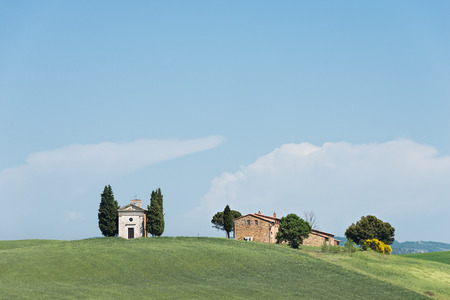 orcia: Cappella della Madonna di Vitaleta church with cypress trees and a farm in a field in the Orcia Valley in Tuscany, Italy.