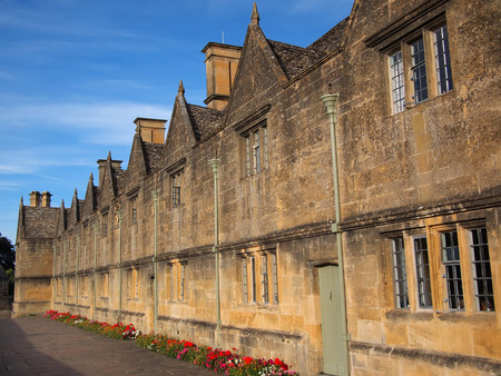 british english: The Almshouses built out of Cotswold stone with stone tiles on the roof, called slates, built in 1612 to house the poor in Chipping Campden, the Cotswolds, England, UK.