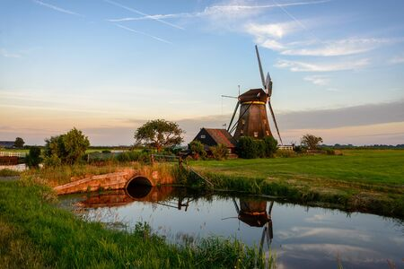 agricultural area: Windmill next to a canal with a bridge in an agricultural area in the countryside in Holland at sunset in Aarlanderveen, in the dutch Green Heart.