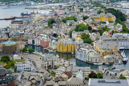 alesund: Norway - June 15, 2014: Aerial view of the colorful Art Nouveau architecture of the city of  lesund, located on various islands at the west coast of Norway in the county of re og Romsdal, seen from Fjelstua viewpoint on Aksla mountain.