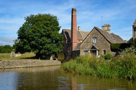 molino de agua: El molino de agua 'antiguo molino' con la chimenea y el agua del río de los ojos, ya que actúa como un museo en la Baja Masacre cerca de Bourton-on-the-Water en el Cotswolds, Gloucestershire, Inglaterra, Reino Unido.