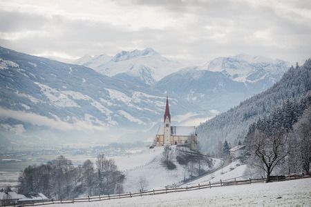fuegen: St. Pankraz church in an alpine landscape in the snow surrounded by clouds and fog on a hill with a sublime view over Zillertal valley with the Alps mountains in the background in Fuegen, Austria in winter.