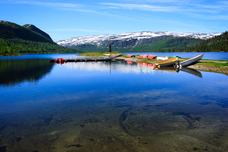 A landscape in Norway with multiple colorful boats drying on the shore of a lake surrounded by mountains. Stock Photo