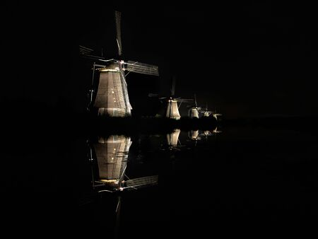 lighted: Five illuminated windmills, lighted by floodlights, with reflection in the water of the canal in the dark black night creating an almost surreal landscape in Kinderdijk, the Netherlands.