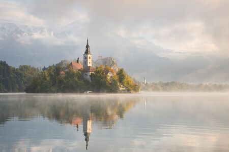 foggy: Church on the small island in Lake Bled and Bled Castle in the first sunlight of sunrise on a beautiful foggy morning in autumn with reflection in the calm water in Slovenia.