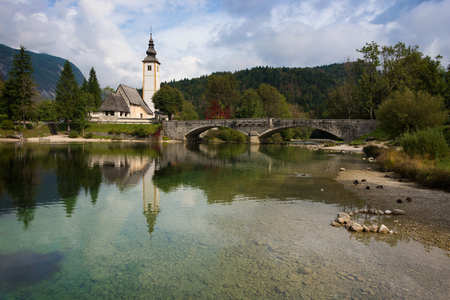 bohinj: Bohinj lake landscape with calm water and reflection of St. John the Baptist church and the stone bridge in Ribcev Laz, Slovenia, at the start of autumn season.