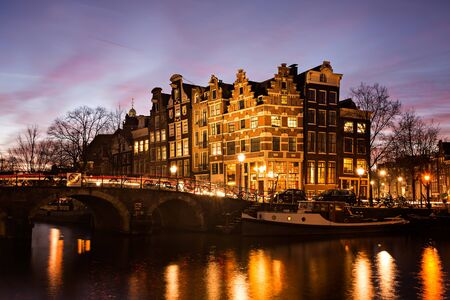 prinsengracht: Amsterdam canal houses in traditional style next to a bridge over Prinsengracht en Brouwersgracht canals illuminated at dusk during Blue Hour in the Netherlands.