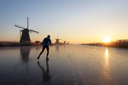 lonely person: Lonely person ice skating past several windmills on the frozen river at sunrise in the early morning in Kinderdijk, the Netherlands in the dutch winter.
