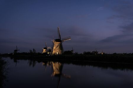 frequented: Several illuminated windmills with reflection in the water of the river at twilight in the beginning of the night in Kinderdijk, the Netherlands. , frequented by tourists and close to Rotterdam.