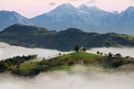 The church of St. Thomas (Sveti Tomaz) on a hilltop in the Slovenian countryside near Skofja Loka surrounded with fog with in the background snow on the peaks of the Slovenian Kamnik Alps during a pink sunrise in Slovenia. Stock Photo