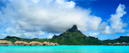 otemanu: Panorama image of a tropical Bora Bora landscape with green Otemanu mountain behind a luxury resort in the turquoise lagoon of the island near Tahiti in Pacific French Polynesia.