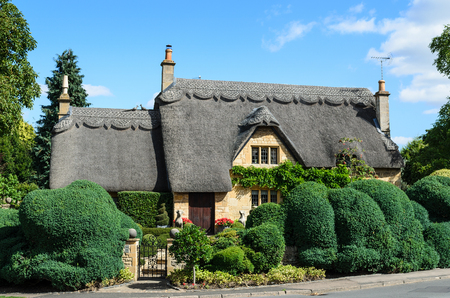 An English thatched cottage built out of Cotswold stone with a beautiful hedge in the garden in Chipping Campden, the Cotswolds, England, UK.