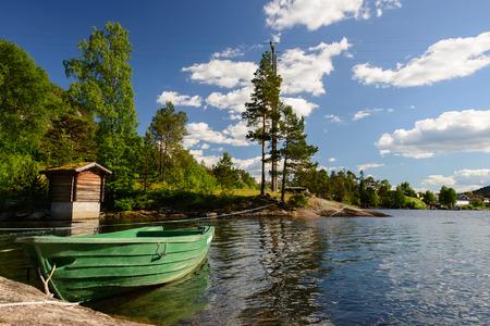 Een landschap met een groene roeiboot in het water onder sommige bomen aan de rand van het fjord in Noorwegen. Stockfoto