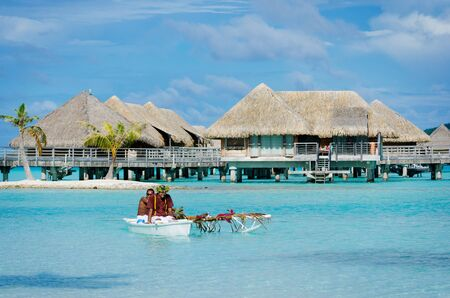 Bora Bora, French Polynesia – May 6, 2012: Room service polynesian style by two men in an outrigger canoe giving breakfast service to honeymoon couples in overwater bungalows in a luxury resort on tropical island Bora Bora, French Polynesia. Editorial
