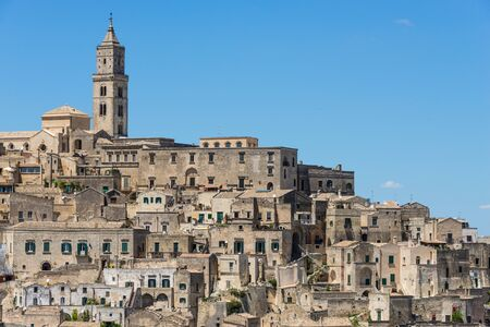 Old houses and a church in ancient architecture in the same kind of stone in a town built upon a hill, known as the Sassi di Matera in Basilicata, Italy. Stock Photo
