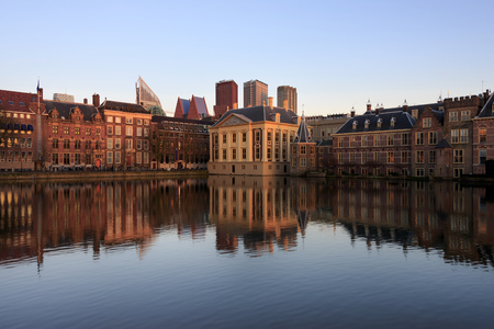 Historic architecture of the Hague, seat of government, like government building, the tower in which the prime minister holds office and Mauritshuis museum with modern buildings in the background with reflection in the water of Hofvijver lake in the Nethe