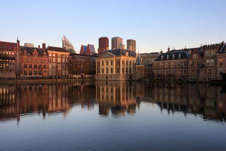 Historische architectuur van Den Haag, zetel van de overheid, zoals overheidsgebouw, de toren waarin de eerste minister kantoor houdt en het Mauritshuis met moderne gebouwen op de achtergrond met weerspiegeling in het water van het Hofvijver-meer in de Nethe
