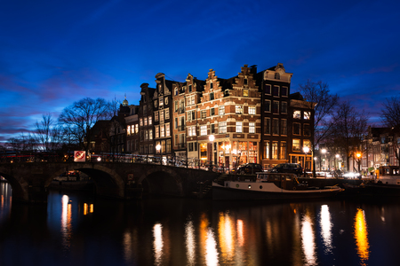 Typical Amsterdam canal houses in historic architecture built in the 17th century along the canals Brouwersgracht and Prinsengracht with a bridge over the water, illuminated at the Blue Hour of dusk in the capital of the Netherlands. Stock Photo