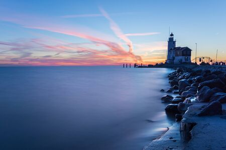 The lighthouse Paard van Marken on Marken island near Volendam and Amsterdam on a cold morning with ice on the rocks that form the pier into IJsselmeer lake at sunrise during the Blue Hour in the Netherlands.