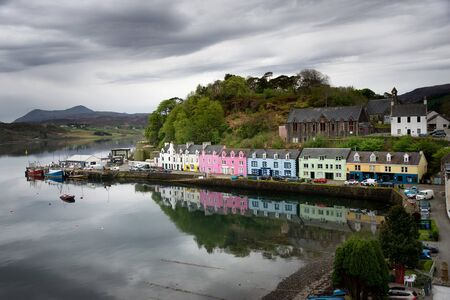 The colorful rainbow houses with reflection in the still water of the fishing harbor of Portree on an overcast day on the Isle of Skye, Inner Hebrides in Scotland, UK. Stockfoto