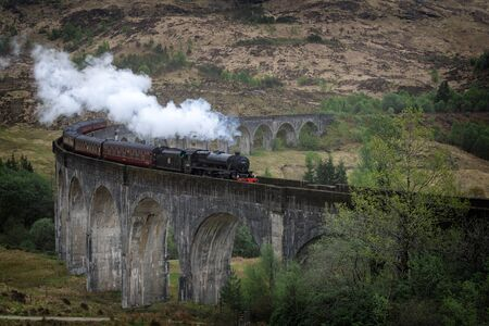 The traditional Jacobite steam train portraited as the Hogwarts Express in the famous Harry Potter movies on the high Glenfinnan railway viaduct in a landscape in the west Highlands of Scotland, UK. Stock fotó